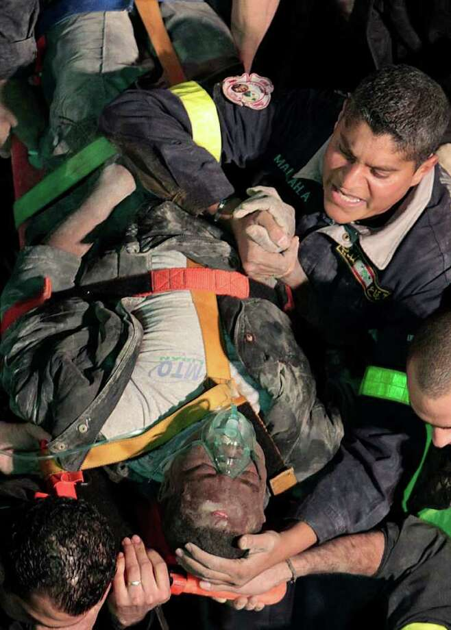 A Lebanese civil defence worker, carries a wounded man after they remove him from beneath rubble of a collapsed buildin, in Beirut, Lebanon, on Sunday Jan. 15, 2012.  Lebanese security officials say an old five-story residential building in Beirut has collapsed. At least seven injured an 15-year-old girl was killed when the building suddenly disintegrated in Beirut's Ashrafieh district.  (AP Photo/Hussein Malla) Photo: Hussein Malla / AP