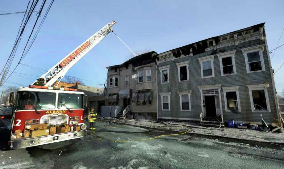 Despite single digit temperatures Albany firefighters continue to wet down a multi-alarm fire that hit 183-187 Sherman Street in Albany, N.Y. Jan. 16, 2012 displacing 30 people.  (Skip Dickstein / Times Union) Photo: SKIP DICKSTEIN