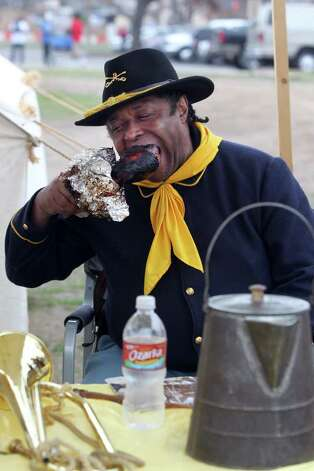 Allan Budd of the Bexar County Buffalo Soldiers enjoys a turkey leg as the Martin Luther King Day celebration at Pittman Sullivan park gets under way. Photo: SAN ANTONIO EXPRESS-NEWS