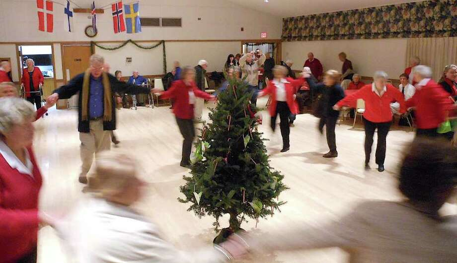 Celebrants of Tjugondag Knut --- the 20th day after Christmas in Scandinavian cultures -- dance around a Christmas tree, before tossing it outdoors, during festivities Saturday night at the Scandinavian Club In Fairfield. Photo: Mike Lauterborn / Fairfield Citizen contributed