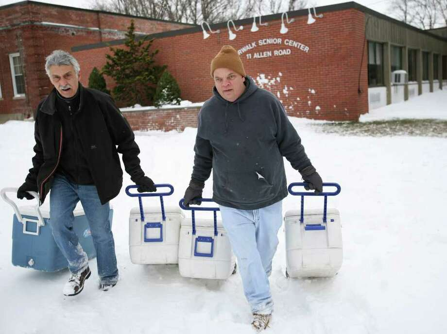 Norwalk Senior Center director Paul Palermo, left, and head of maintenance David Clinchy, pull coolers filled with meals for seniors across the snow outside the snowed in center on Tuesday, December 28, 2010. Palermo said they doing a double delivery to make up for the fact that on Monday, for the first time in his memory, Meals on Wheels was unable to deliver because of the road conditions. Photo: Brian A. Pounds, ST / Connecticut Post