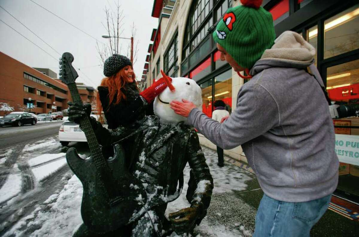 Brittany Doyle and Stuart Haury turn the Jimi Hendrix statue on Broadway Ave. outside of Blick Art Materials into a snowman in Seattle on Sunday, Jan. 15, 2012. (Photo by Lindsey Wasson).