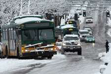 Buses stuck on Jefferson St. near the intersection of Jefferson St. and 12th Ave. in Seattle on Sunday, Jan. 15, 2012. Snow in Seattle has made it difficult for vehicles to maintain traction on the roads.
