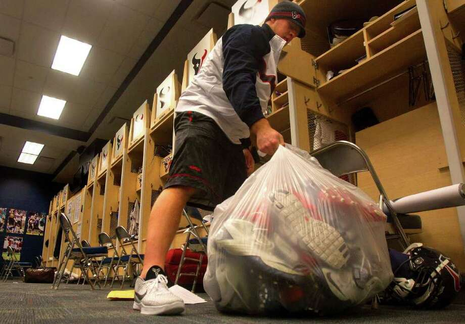 Houston Texans defensive end J.J. Watt empties out his locker inside the Texans locker room at Reliant Stadium Monday, Jan. 16, 2012, in Houston. Photo: Cody Duty, Houston Chronicle / © 2011 Houston Chronicle