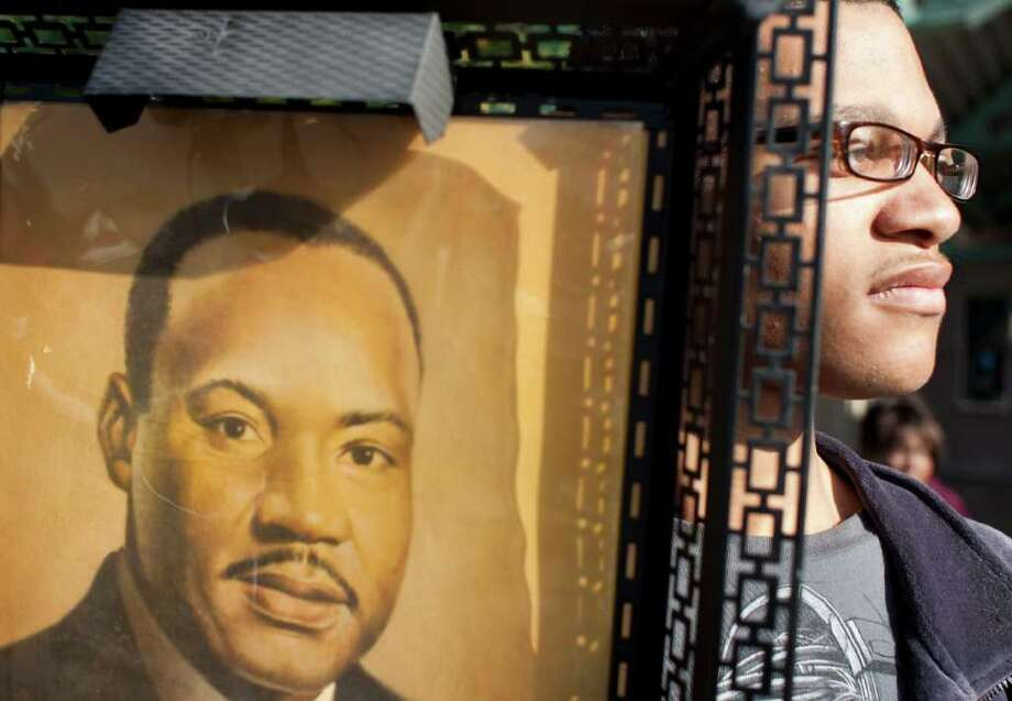 "Christon Whitfield, 19, holds up a vintage framed picture of Martin Luther King as he watches the 34th Annual ""Original"" Dr. Martin Luther King Birthday Parade and Celebration Monday, Jan. 16, 2012, in Houston. Photo: Nick De La Torre, Houston Chronicle / © 2012  Houston Chronicle"