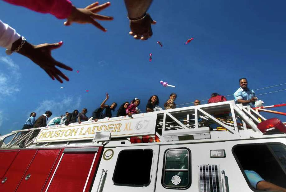 Spectators reach for candy thrown from Houston Ladder XL 67 during the Martin Luther King Day parade on San Jacinto St., Monday, Jan. 16, 2012, in Houston. Photo: Cody Duty, Houston Chronicle / © 2011 Houston Chronicle