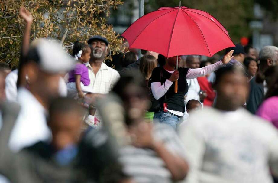 Spectators wave during the Martin Luther King Day parade on San Jacinto St., Monday, Jan. 16, 2012, in Houston. Photo: Cody Duty, Houston Chronicle / © 2011 Houston Chronicle