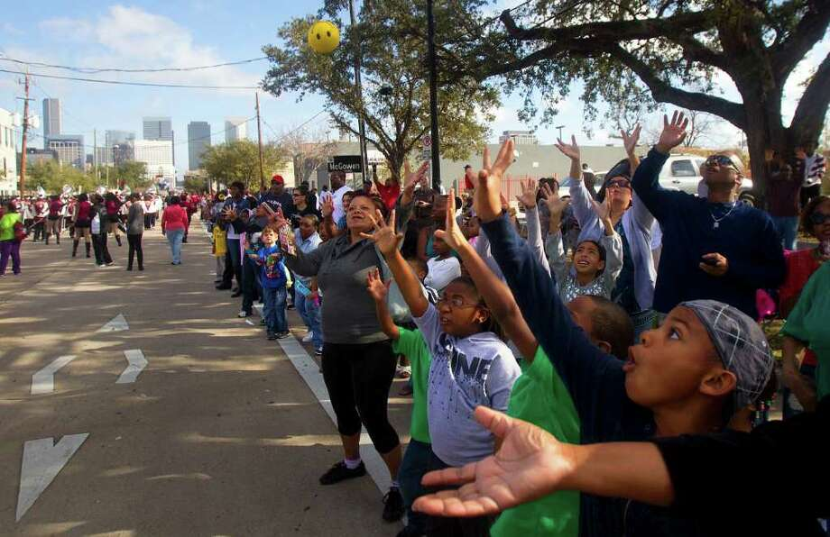Spectators reach for a ball thrown from the Houston Community College float during the Martin Luther King Day parade on San Jacinto St., Monday, Jan. 16, 2012, in Houston. Photo: Cody Duty, Houston Chronicle / © 2011 Houston Chronicle