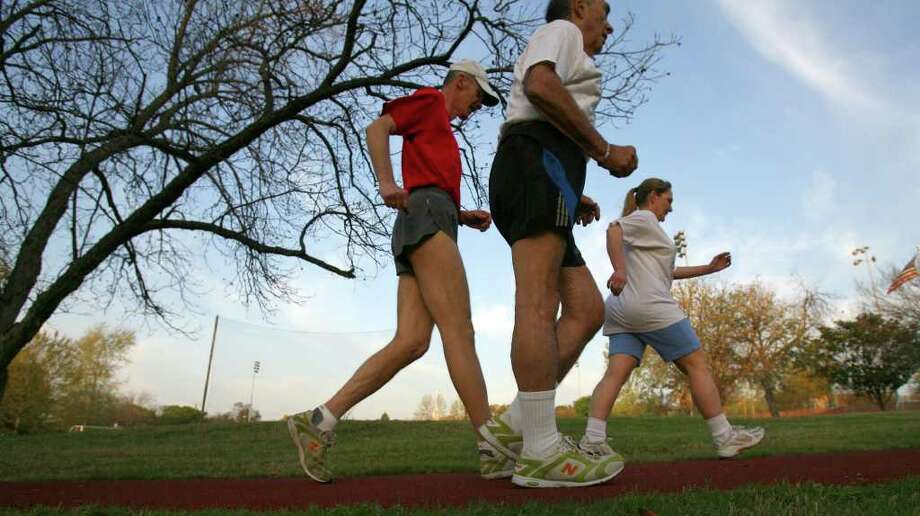 """Racewalkers Victoria Cruz (front), Leonard Stern (center) and Bert Pickell (rear) walk briskly on the trail going around the soccer field at Trinity University. Stern says, """"a body in motion stays in motion.  JOHN DAVENPORT / STAFF / SAN ANTONIO EXPRESS-NEWS"""