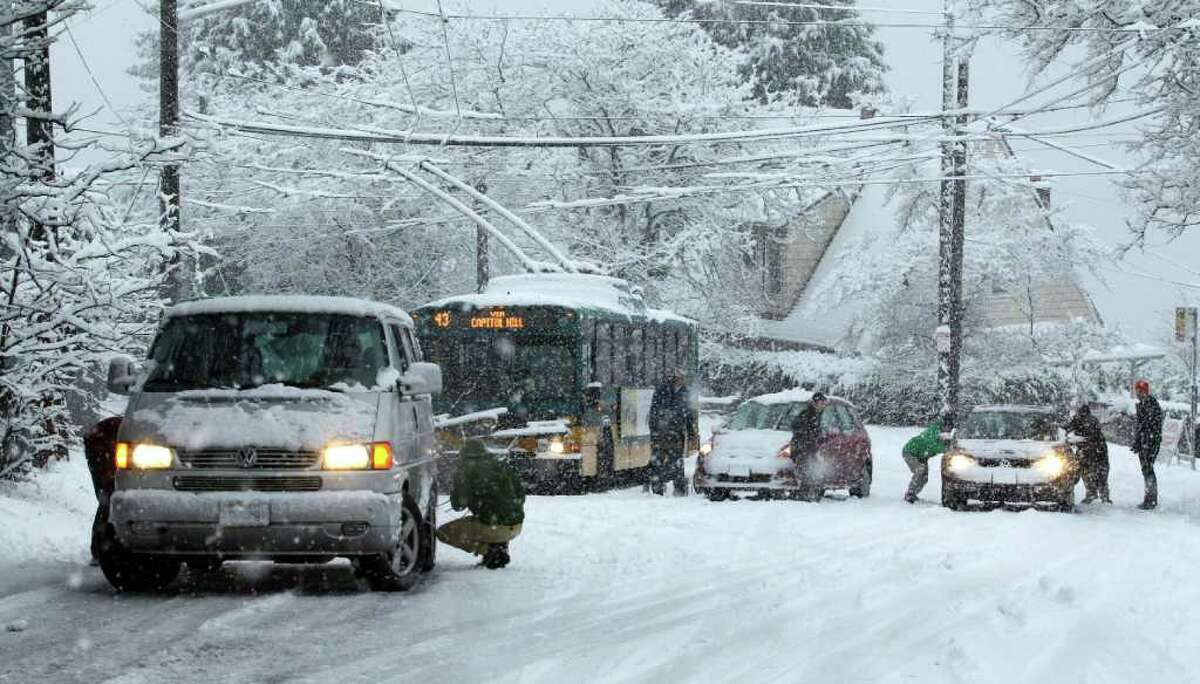Cars and a bus sit stuck on a hill on 24th Avenue East during a snowstorm in Seattle, Sunday, Jan. 15, 2012. Several inches of snow fell quickly Sunday morning, snarling traffic and clogging roadways.