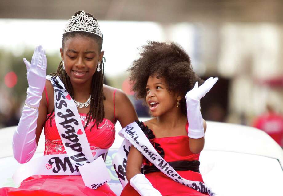 "Tamirah Collins, 13, left, and Asha Malivers, 7, finalists of the Little Miss Happy Headed Natural Hair Pageant, talk as they wave and blow kisses to the crowd during the 34th Annual ""Original"" Dr. Martin Luther King Birthday Parade and Celebration Monday, Jan. 16, 2012, in Houston. Photo: Nick De La Torre, Houston Chronicle / © 2012 Houston Chronicle"