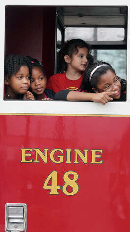 Kids riding in the San Antonio Fire Department's engine 48 enjoy the 25th Martin Luther King, Jr. March on their way to the celebration at Pittman Sullivan park on Martin Luther King Day. Photo: JOHN DAVENPORT, John Davenport / SAN ANTONIO EXPRESS-NEWS (Photo can be sold to the public)
