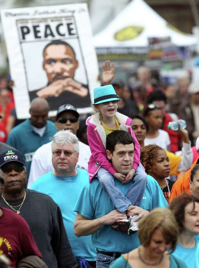 Jeremy Bergeron carries his daughter Katherine Bergeron,8, (wearing blue hat) on his shoulders down Martin Luther King boulevard Monday January 16, 2012 during the Martin Luther King, Jr. march. This was Katherine's third time to walk the march. Photo: JOHN DAVENPORT, John Davenport / SAN ANTONIO EXPRESS-NEWS (Photo can be sold to the public)