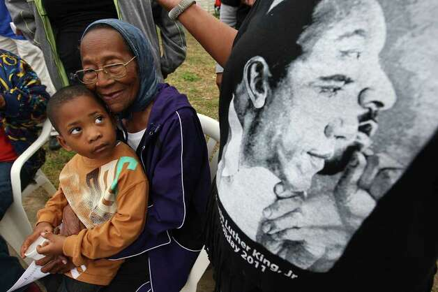 Gloria Nelson, 86, holds her great-great-grandson, Korvan Franklin, 4, as they watch the City of San Antonio Martin Luther King, Jr., 25th anniversary Commemorative March, Monday, Jan. 16, 2012. For the past 25 years, Nelson has gathered with family at her daughter's house on the 3500 block of Martin Luther King Drive to watch the march. Photo: JERRY LARA, San Antonio Express-News / SAN ANTONIO EXPRESS-NEWS