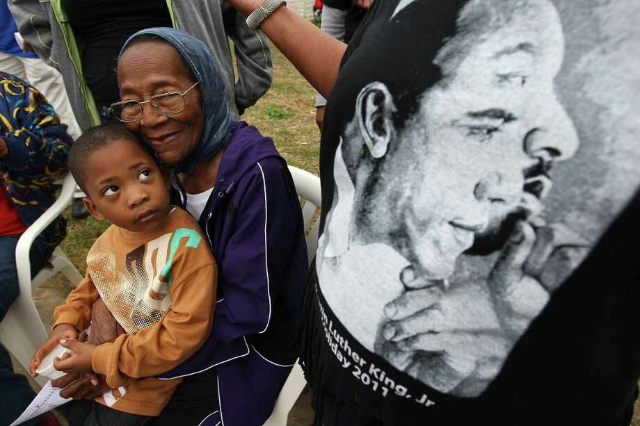METRO -- Gloria Nelson, 86, holds her great-great-grandson, Korvan Franklin, 4, as they watch the City of San Antonio Martin Luther King, Jr., 25th anniversary Commemorative March, Monday, Jan. 16, 2012. For the past 25 years, Nelson has gathered with family at her daughter's house on the 3500 block of Martin Luther King Drive to watch the march.  JERRY LARA/glara@express-news.net Photo: JERRY LARA, San Antonio Express-News / SAN ANTONIO EXPRESS-NEWS