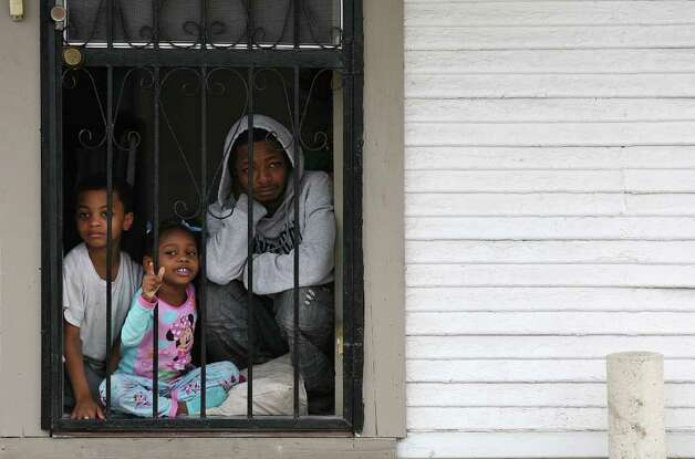 "The Stacker family watch as over tens of thousands walk by their house during the City of San Antonio Martin Luther King, Jr., 25th anniversary Commemorative March, Monday, Jan. 16, 2012. This year's theme was ""Journey Beyond the March...Live Beyond the Dream"". From left are Malcolm, 6, Symone, 4, and Jamaal Stacker, 30. Photo: JERRY LARA, San Antonio Express-News / SAN ANTONIO EXPRESS-NEWS"