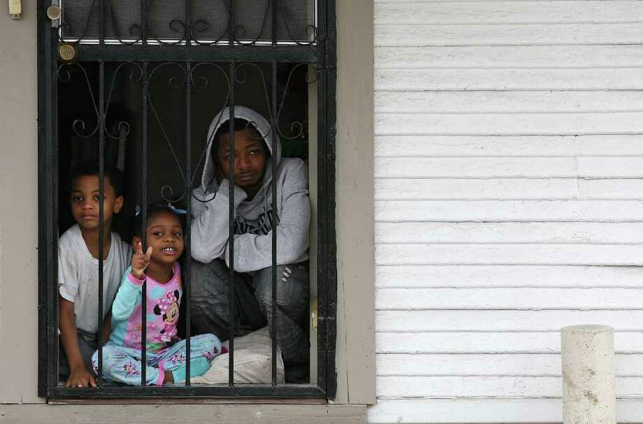 "METRO -- The Stacker family watch as over tens of thousands walk by their house during the City of San Antonio Martin Luther King, Jr., 25th anniversary Commemorative March, Monday, Jan. 16, 2012. This year's theme was ""Journey Beyond the March...Live Beyond the Dream"". From left are Malcolm, 6, Symone, 4, and Jamaal Stacker, 30. JERRY LARA/glara@express-news.net Photo: JERRY LARA, San Antonio Express-News / SAN ANTONIO EXPRESS-NEWS"