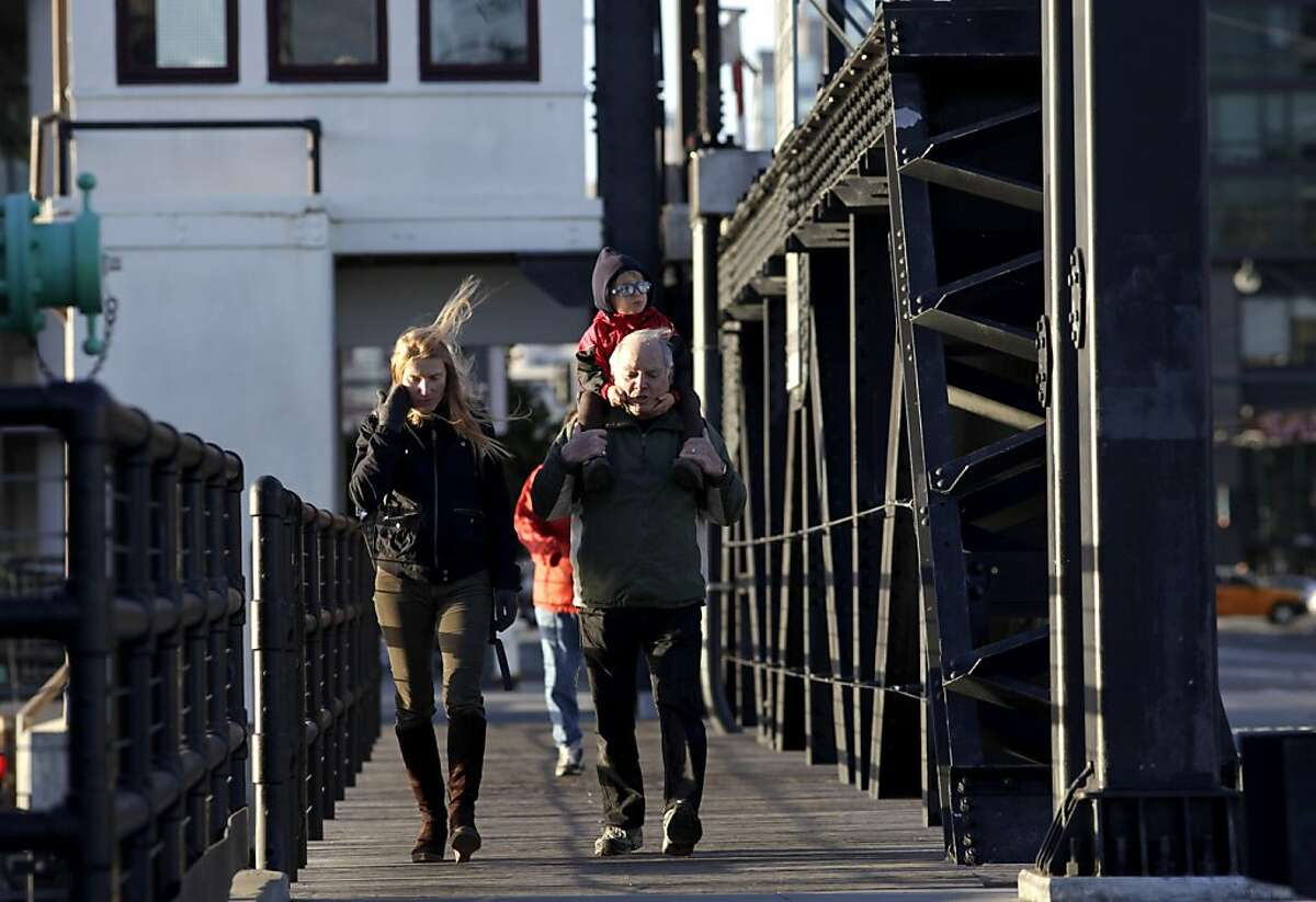 Families walk over the bridge that crosses Mission Creek, Sunday, January 15, 2012, where new condo buildings have sprung up in the past few years.