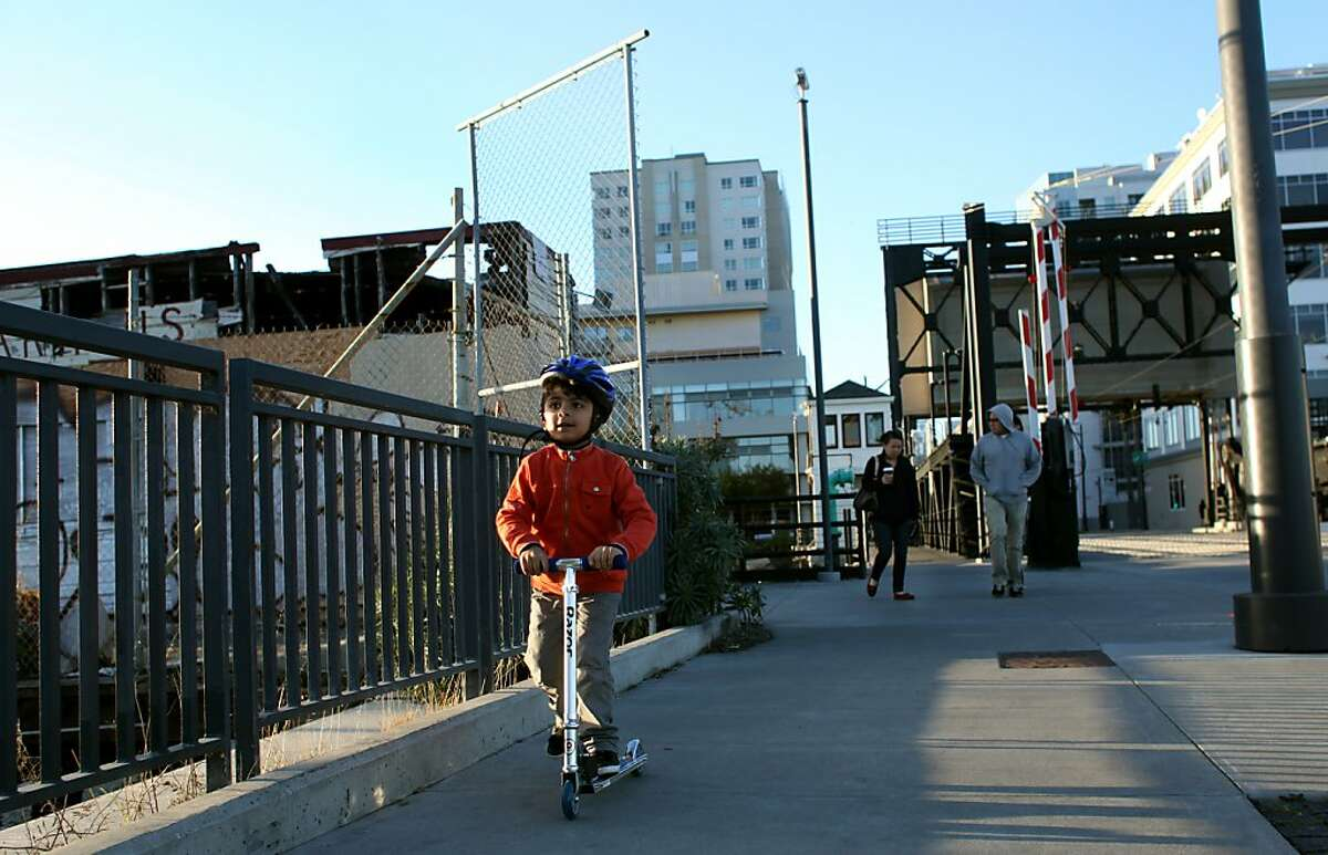 Families walk along the bridge across Mission Creek, Sunday, January 15, 2012, where new condo buildings have sprung up in the past few years.