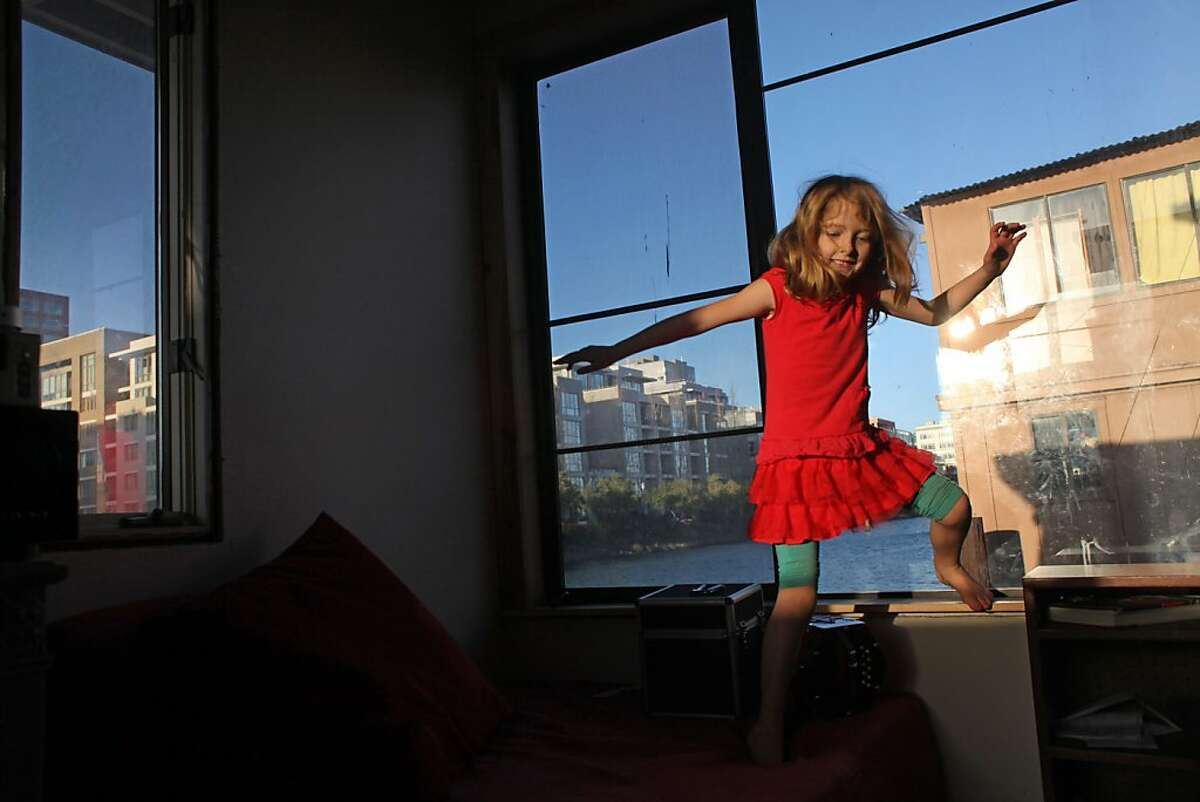 Olivia Lytle, 7 years-old, plays in the window of her home on the water, Sunday January 15, 2012, along Mission Bay Creek in San Francisco, Calif. Their are 20 house boats in San Francisco now surrounded by new condo buildings which has developed in the past few years.