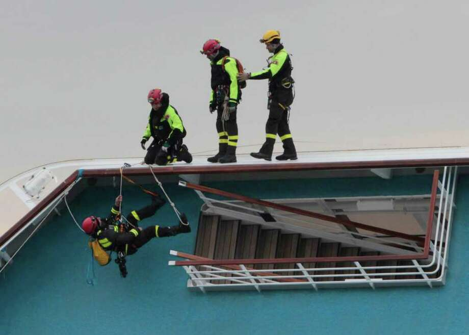 Italian firefighter scuba divers work on the Costa Concordia two days after it ran aground near Giglio, Italy. Officials say a passenger's body has been found, raising the death toll to six. Photo: Gregorio Borgia, Associated Press / AP