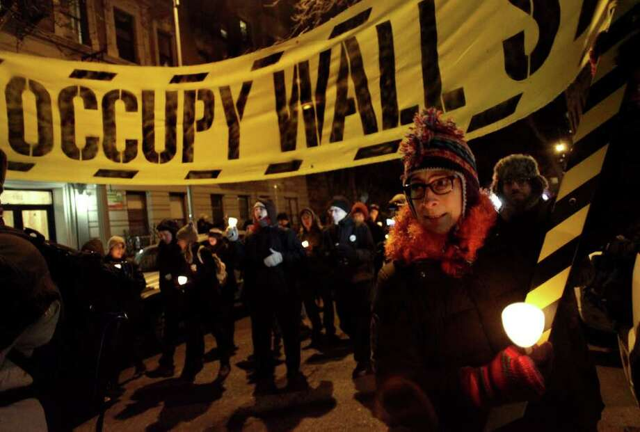 Participants, including Occupy Wall Street protesters, march and take part in a candlelight vigil to honor Rev. Martin Luther King, Jr. in New York, Sunday, Jan. 15, 2012. The march started at Cathedral Church of Saint John the Divine, ending at nearby Riverside Church where a ceremony took place with speeches, song and poetry honoring the civil right leader. (AP Photo/Craig Ruttle) Photo: Craig Ruttle