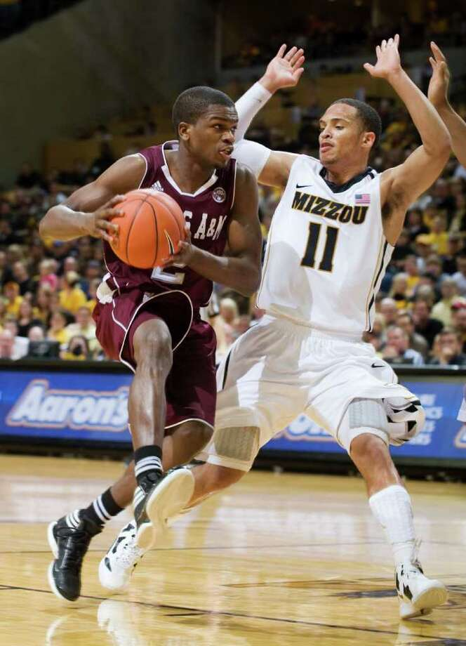 Texas A&M's Naji Hibbert, left, dribbles past Missouri's Michael Dixon during the first half of an NCAA college basketball game Monday, Jan. 16, 2012, in Columbia, Mo. (AP Photo/L.G. Patterson) Photo: L.G. PATTERSON, Associated Press / FR23535 AP