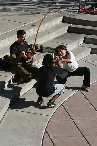 Vanessa Quezada playing capoeira with Jarrel Phillips (middle), as Jian Giannini (left) plays the barimbau on top of the roof of the Moscone convention center San Francisco, Calif., on Monday, January 16, 2012.  They are from a group called Capoeira IJEXç established by Mestre Urubu Malandro in 1996. Photo: Liz Hafalia, The Chronicle