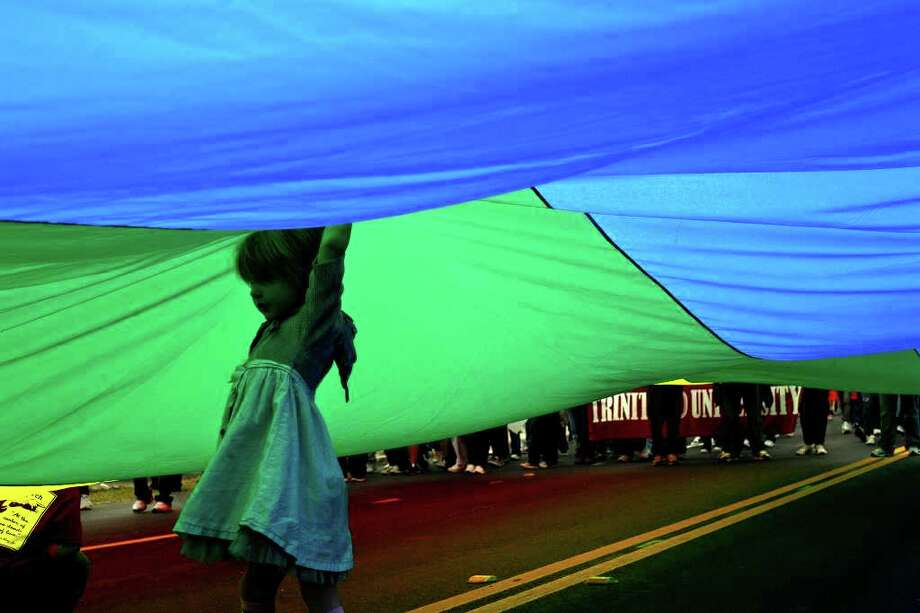 metro - Harriet Martin, 5, plays underneath a rainbow flag during the Martin Luther King, Jr. March in San Antonio on Monday, Jan. 16, 2012. BRIA WEBB/For the Express-News Photo: BRIA WEBB , SAN ANTONIO EXPRESS-NEWS / Bria Webb