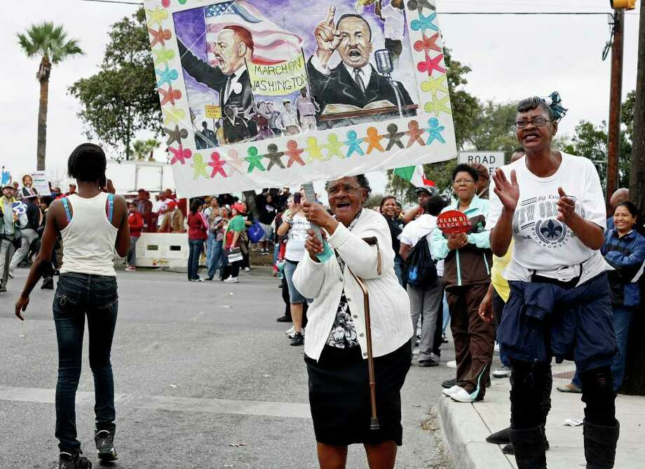 metro - Clara Hunt, center, and Karen Natre, right, congratulate marchers as they finish the march during the Martin Luther King, Jr. March in San Antonio on Monday, Jan. 16, 2012. BRIA WEBB/For the Express-News Photo: BRIA WEBB , SAN ANTONIO EXPRESS-NEWS / Bria Webb