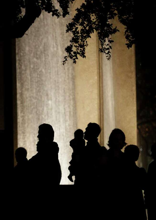 People gather at the Water Wall near the Galleria in vigil for Gelareh Bagherzadeh, who was killed Monday, Jan. 16, 2012, in Houston. The 30-year-old female student at the Texas Medical Center was found shot to death in a car at a residence in the 800 block of Augusta near Sugar Hill near the Galleria early Monday morning. Photo: Melissa Phillip, Houston Chronicle / © 2011 Houston Chronicle