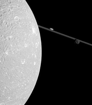 """This NASA handout image released January 16, 2012 shows Saturn's moon Dione(L), which includes two smaller moons, Epimetheus and Prometheus, near the planet's rings. The image was taken in visible light with Cassini's narrow-angle camera during the spacecraft's flyby of Dione on Dec. 12, 2011. Dione (698 miles, or 1,123 kilometers across) is closest to Cassini here and is on the left of the image. Potato-shaped Prometheus (53 miles, or 86 kilometers across) appears above the rings near the center top of the image. Epimetheus (70 miles, or 113 kilometers across) is on the right. This view looks toward the northern, sunlit side of the rings from less than one degree above the ring plane. The view was acquired at a distance of approximately 67,000 miles (108,000 kilometers) from Dione.  = RESTRICTED TO EDITORIAL USE - MANDATORY CREDIT """" AFP PHOTO / NASA/JPL-Caltech/Space Science Institute """" - NO MARKETING NO ADVERTISING CAMPAIGNS - DISTRIBUTED AS A SERVICE TO CLIENTS = Photo: HO, AFP/Getty Images / AFP"""
