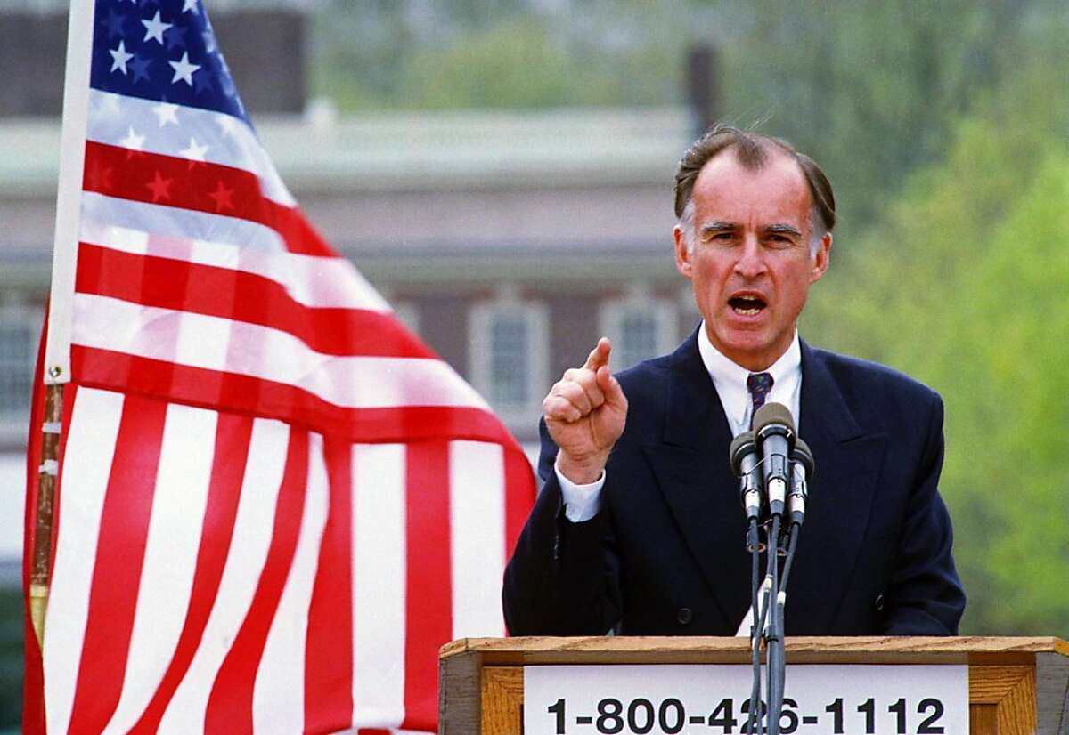 Democratic presidential contender Jerry Brown gestures during a noontime rally in the Olde City section of Philadelphia with Independence Hall in the background, April 27, 1992. Brown's toll-free campaign number adorns the front of the rostrum. (AP Photo/Carol Francavilla)