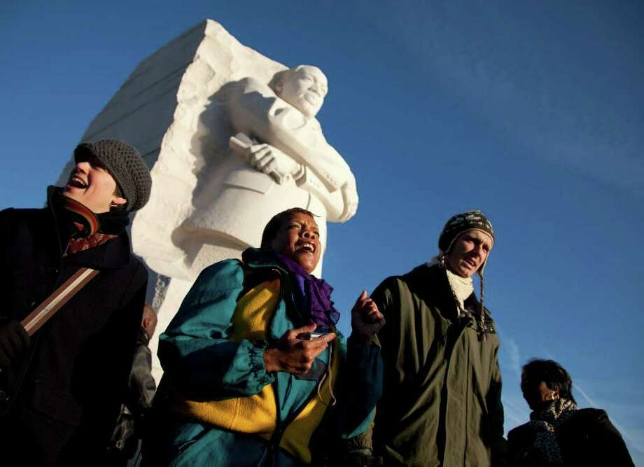 From left, Liza Joy Marcato of Hillsdale, N.Y., Beverly Steed of Washington, and Marcus Knausenberger of Devin, Pa., sing after a ceremony at the Martin Luther King, Jr. Memorial in Washington, Monday, Jan. 16, 2012.  (AP Photo/Evan Vucci) Photo: Evan Vucci