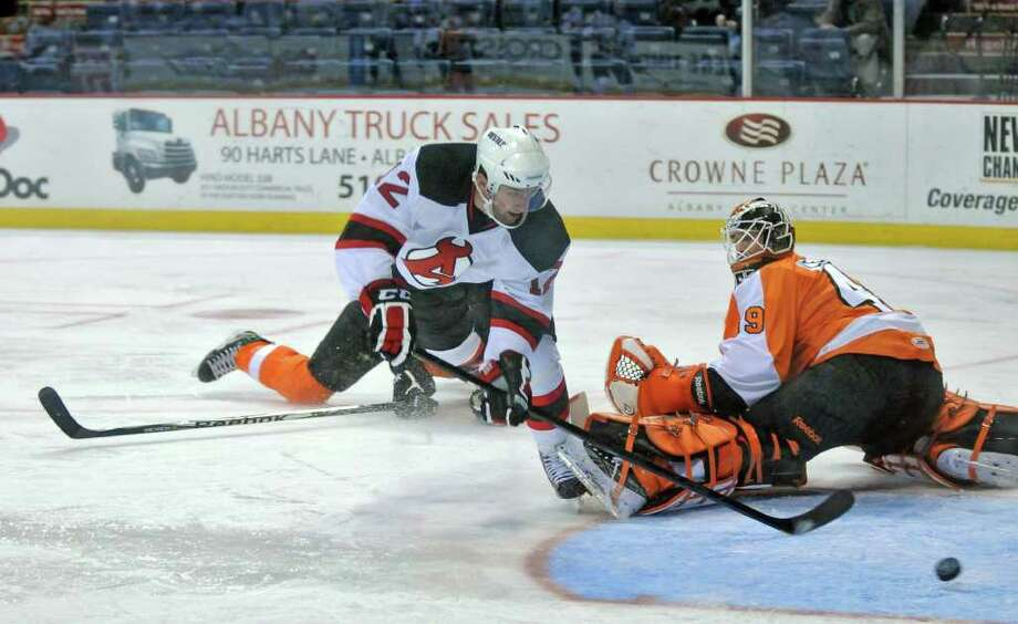 Albany Devils player Tim Sestito goes airborne while scoring on  Adirondack Phantoms goalie Michael Leighton to make the score 4-0 in the second period of Albany's 5-3 victory at the Times Union Center on Monday afternoon Jan. 16, 2012 in Albany, NY.  (Philip Kamrass / Times Union ) Photo: Philip Kamrass / 10015984B