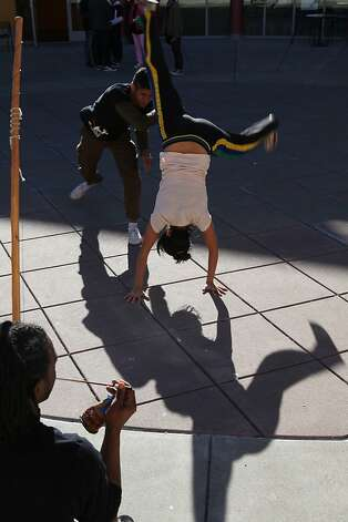 Vanessa Quezada playing capoeira with Jian Giannini (top) as Jarrel Phillips (bottom left) plays the barimbau on top of the roof of the Moscone convention center San Francisco, Calif., on Monday, January 16, 2012.  They are from a group called Capoeira IJEXç established by Mestre Urubu Malandro in 1996. Photo: Liz Hafalia, The Chronicle