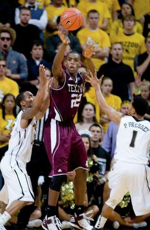 Texas A&M's Khris Middleton, center, passes the ball as Missouri's Marcus Denmon, left, and Phil Pressey, right, defend during the second half of an NCAA college basketball game Monday, Jan. 16, 2012, in Columbia, Mo. Missouri won 70-51. Photo: Associated Press, L.G. Patterson / FR23535 AP