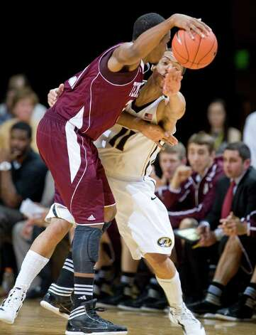 Missouri's Michael Dixon, right, reaches in to knock the ball away from Texas A&M's Khris Middleton during the second half of an NCAA college basketball game Monday, Jan. 16, 2012, in Columbia, Mo. Missouri won 70-51. Photo: Associated Press, L.G. Patterson / FR23535 AP