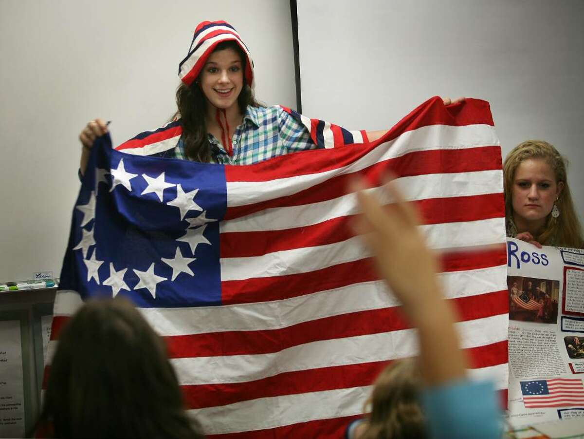 Elise Sondheim, left, and Sofia Filan, juniors at Fairfield Warde High School, give presentations based on their U.S. History research projects at Stratfield Elementary School in Fairfield, Conn. on Tuesday, October 26, 2009. Sondheim stitched an American flag which she showed the class during her presentation on Betsy Ross.