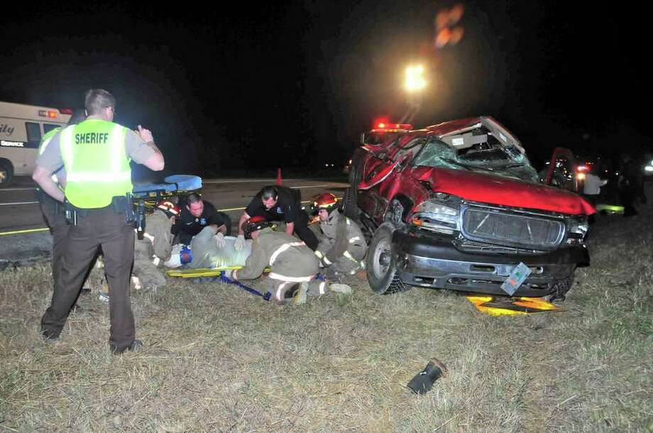 Atascosa County emergency personnel prepare to transport one of three men involved in a one-vehicle wreck late Monday night. Two oilfield workers from Arkansas were killed and a third was injured. Photo: For The Express-News, Xavier J. Garcia
