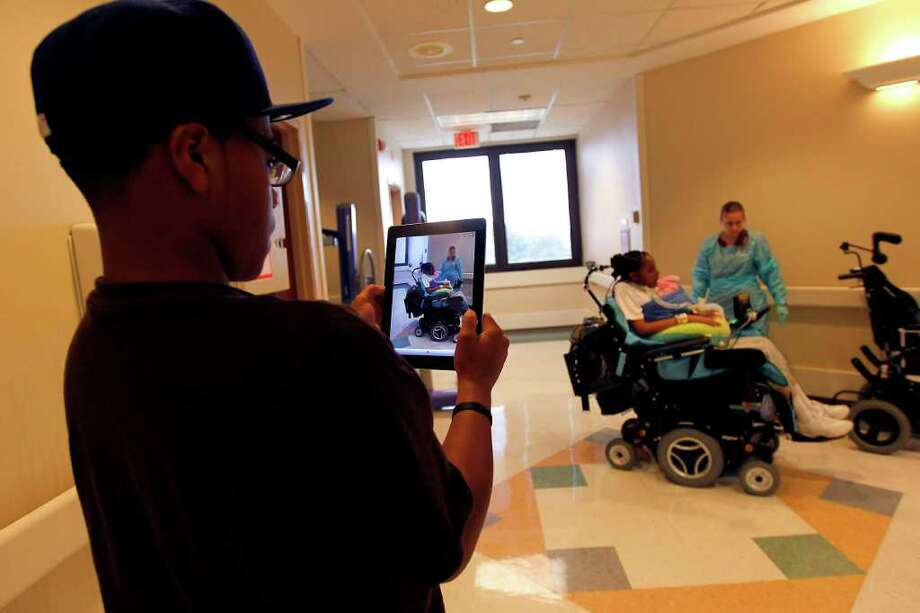 Nicholas Deville, 13, shoots a video of his sister Chyna Young, with his iPad, as Young, 18, a quadriplegic, paralyzed from the neck down rides the hallways of TIRR with her baby, Jada, Nov. 25, 2011. Photo: Karen Warren, Houston Chronicle / © 2011 Houston Chronicle