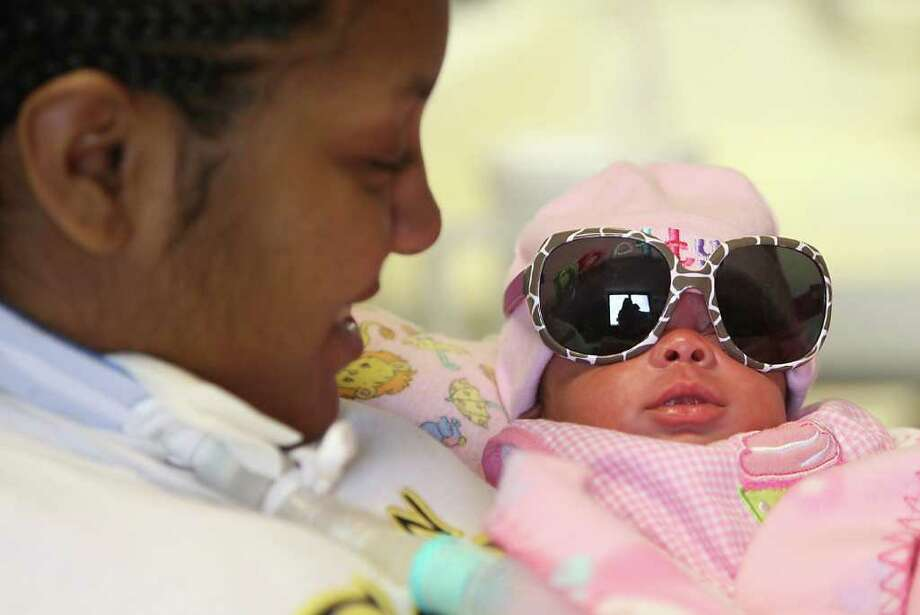 Chyna holds her baby, Jada with a pair of sunglasses on at TIRR, Nov. 25, 2011. Photo: Karen Warren, Houston Chronicle / © 2011 Houston Chronicle