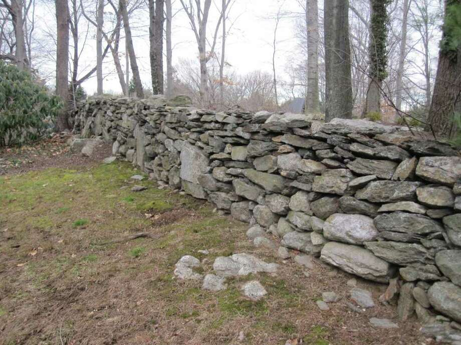 A stone wall on the author's property in Fairfield is just a small stretch of an estimated 250,000 miles of stone walls built by early settlers in Northeast states. Photo: Contributed Photo