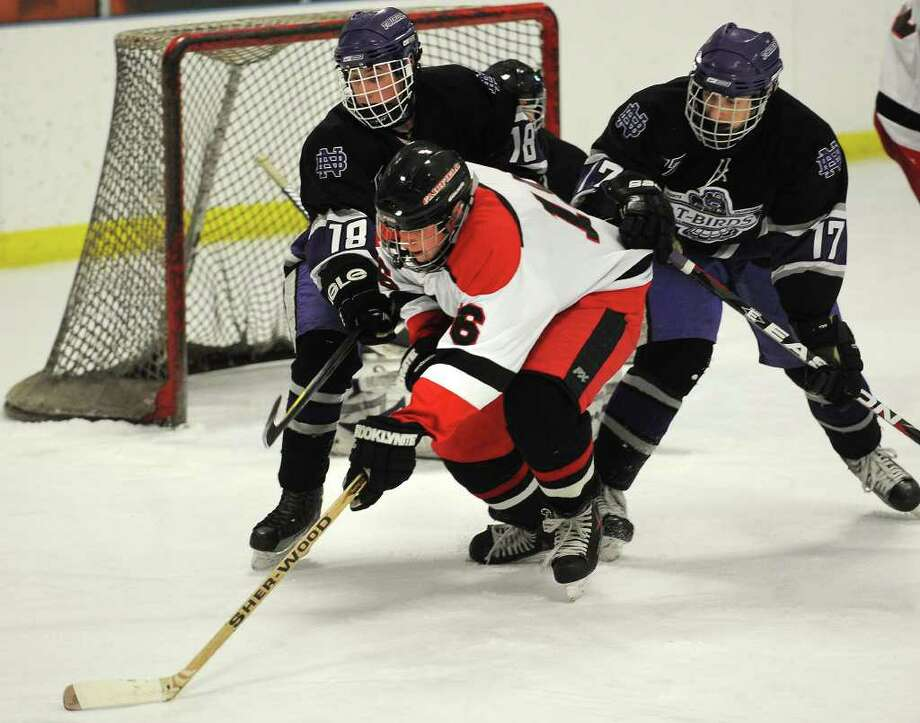 Fairfield's Matt Larouche plays the puck in front of North Branford defenders Brendan Appi, left, and Nick Johnson at the Wonderland of Ice in Bridgeport on Monday, January 16, 2011. Photo: Brian A. Pounds / Connecticut Post
