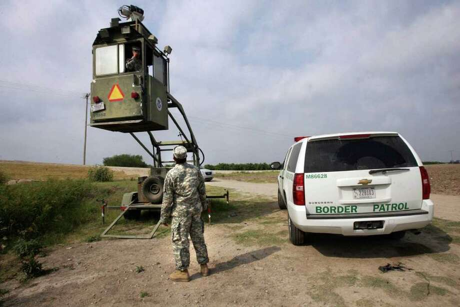 In this April 19, 2011 picture, a member of the National Guard checks on his colleague inside a Border Patrol Skybox near the Hidalgo International Bridge in Hidalgo, Texas. National Guard members along the Texas-Mexico border assist Border Patrol by surveying the terrain from the tower. (AP Photo/Delcia Lopez) Photo: Delcia Lopez, Associated Press / 2011 AP