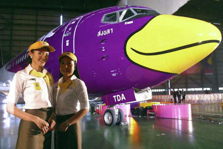 China Airlines promoted a different export -- Taiwanese fruit -- with this airplane design, shown here with Japanese actress Akiko Hinagata, who was named as the Taiwanese fruit ambassador for Japan. Photo: STR, AFP/Getty Images / 2004 AFP