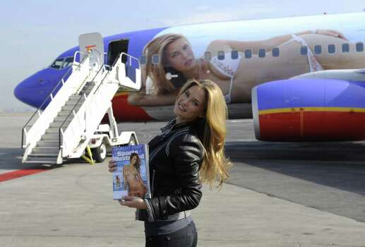 Israeli model Bar Refaeli holds the 2009 cover of Sports Illustrated (SI) swimsuit issue, as she unveils SI One, a Southwest Airlines Boeing 737-700 wrapped with her SI image at La Guardia aiport in New York, February, 11, 2009. SI and Southwest Airlines unveiled the plane which will fly between New York and Las Vegas for a limited time, bearing SI Swimsuit imagery on its fuselage. AFP PHOTO/Emmanuel Dunand Photo: EMMANUEL DUNAND, AFP/Getty Images / 2009 AFP