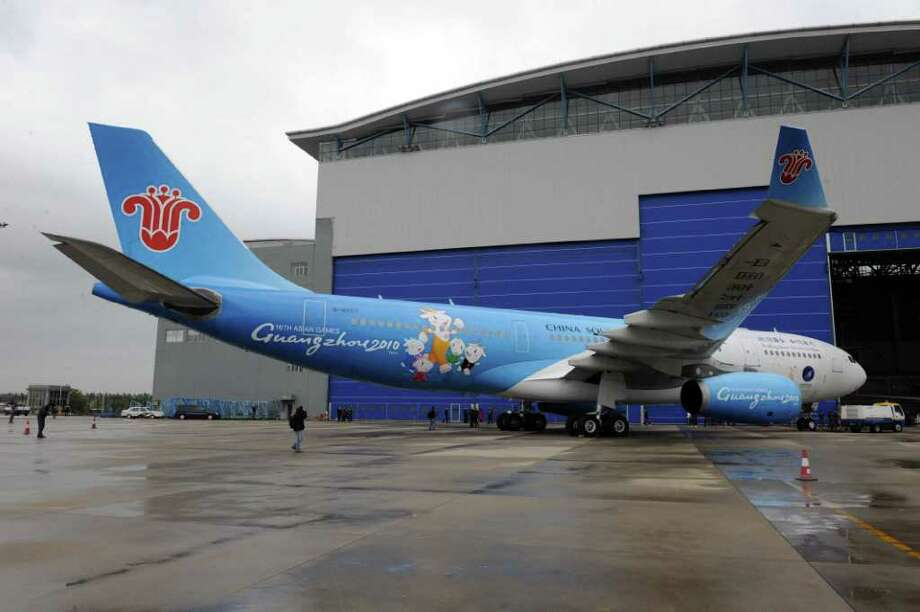FILE-- A China Southern Airlines jetliner painted with the logo and colours of the 2010 Asian Games rolls out from a hangar at the airport in Beijing on November 17, 2009. An elderly Chinese woman sought to invoke good luck by tossing her silver at the jet she was boarding Tuesday. Photo: AFP, AFP/Getty Images / 2009 AFP