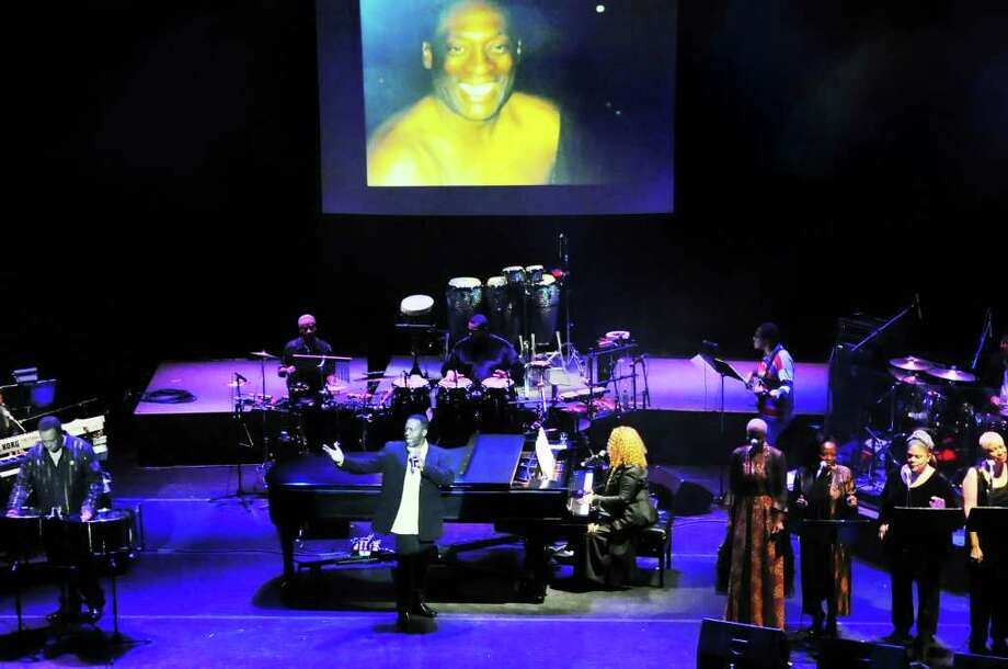 """Dennis Collins, center, and Roberta Flack perform """"Where is the Love"""" as family and friends of the late Ralph MacDonald gather for a memorial service at Stamford's Palace Theatre Monday night in Stamford, Conn., January 16, 2012.  The evening honoring the Grammy Award-winning percussionist and composer featured personal remembrances and musical performances. MacDonald, 67, a longtime Stamford resident, died one month ago on Dec. 18 of lung cancer. Many of the artists MacDonald worked with over the years took to the stage to perform his music, including Bufffet and the Coral Reefer Band, Valerie Simpson and Bobbi Humphrey. As a producer, performer and songwriter, MacDonald earned multiple Grammys, including those for 'Calypso Breakdown,' 'Just The Two of Us' and 'Where is The Love.' Photo: Keelin Daly / Stamford Advocate"""