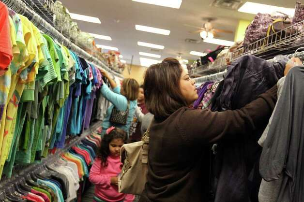 Customers browse the women's clothing at Plato's Closet at North Park Mall, Monday, January 16, 2012. The franchise buys gently used merchandise that would appeal to the teen to twenty-something demographic and sells them at about 70% of retail cost, paying sellers 35% of their floor price. Photo: JENNIFER WHITNEY, Special To The Express-News / special to the Express-News